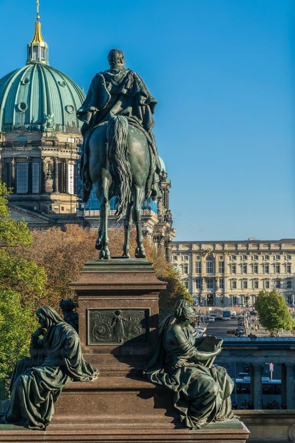 BERLÍN, ALEMANIA - 26 DE SEPTIEMBRE DE 2018: Enfocado debido a la estatua ecuestre de Frederick William IV con la fachada de foto de archivo