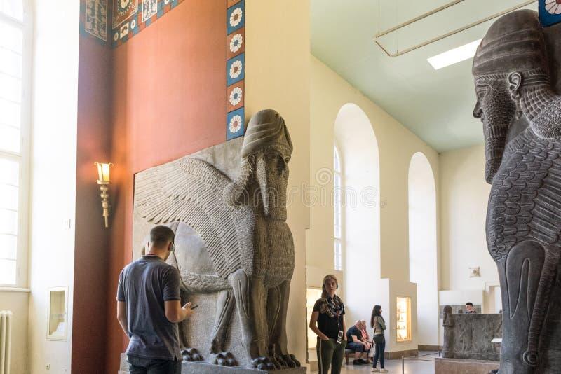 BERLÍN, ALEMANIA - 26 DE SEPTIEMBRE DE 2018: Imagen brillante de los visitantes que miran exposiciones de la estatua de Lamassu,  foto de archivo libre de regalías