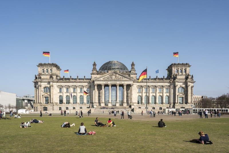 BERLÍN, ALEMANIA, EL 8 DE ABRIL DE 2018: La fachada del edificio de Reichstag en Berlín, muchos visitantes no identificados y tur foto de archivo libre de regalías
