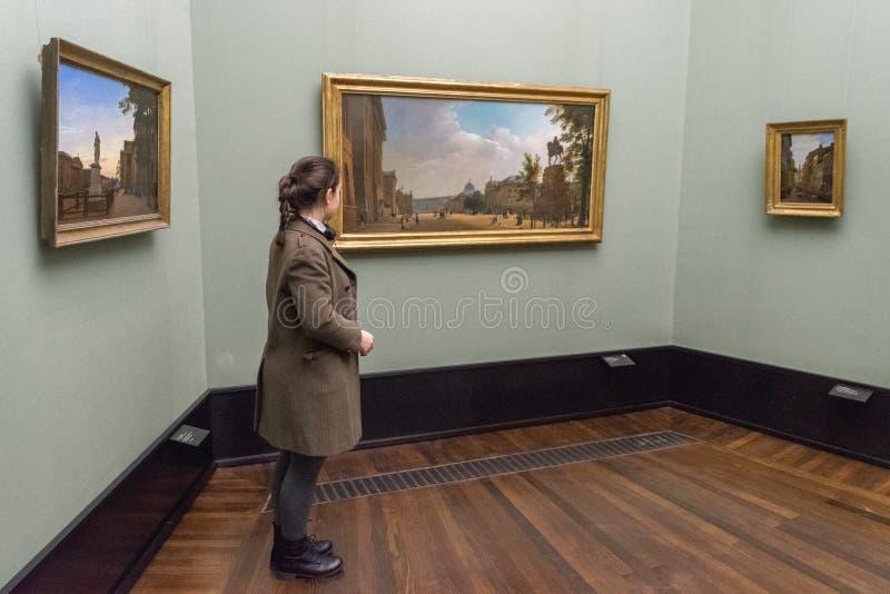BERLÍN - 20 DE OCTUBRE DE 2016: Muchacha que admira pinturas en el Alt famoso imágenes de archivo libres de regalías