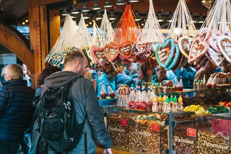Berlín, el 3 de octubre de 2017: La celebración del hombre de Oktoberfest A al lado del contador mira los diversos caramelos trad imagen de archivo