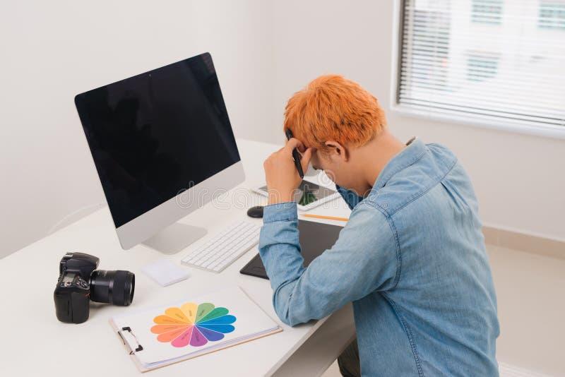 ?berlastungsfunktion Besch?ftigte ?berarbeitende Bilder des Fotografen auf seiner Laptop-Computer von seinem Hauptstudio lizenzfreies stockbild