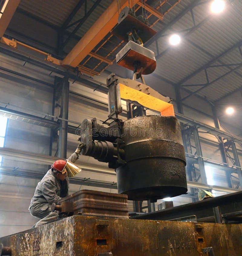 Berlijn, Duitsland - April 18, 2013: Productie van metaalcomponenten in een gieterij - groep arbeiders stock afbeeldingen