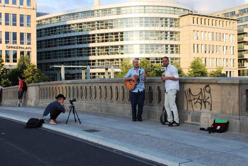 Berlijn, Duitsland: Musici en meisje-fotograaf op de brug in Belin stock foto's