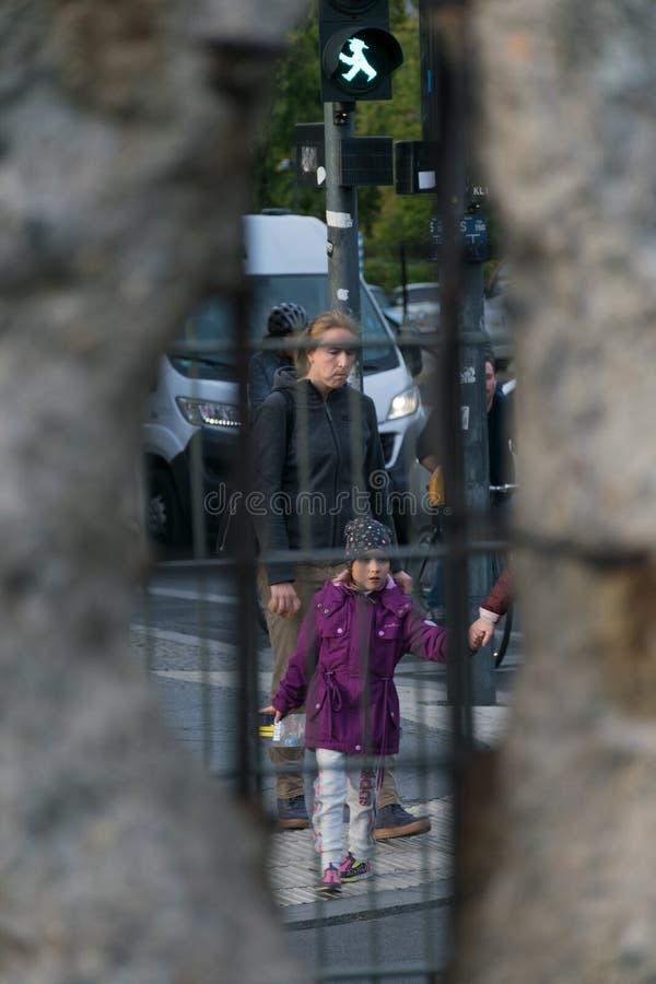 BERLIJN, DUITSLAND - SEPTEMBER 26, 2018: Het tegenover elkaar stellen en nieuwsgierig perspectief door een gat van Berlin Wall va stock fotografie