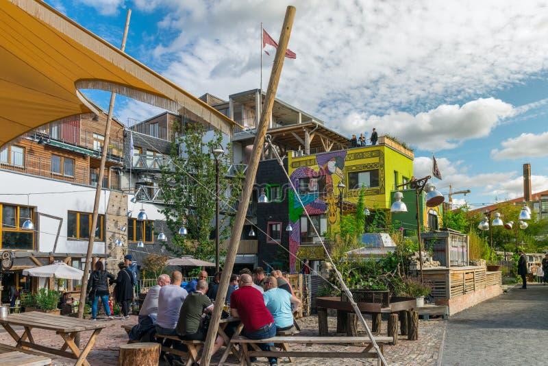 BERLIJN, DUITSLAND - September 26, 2018: Kleurrijk overzicht van een groep mensen die in houten banken bij de bar van het Pampast royalty-vrije stock fotografie