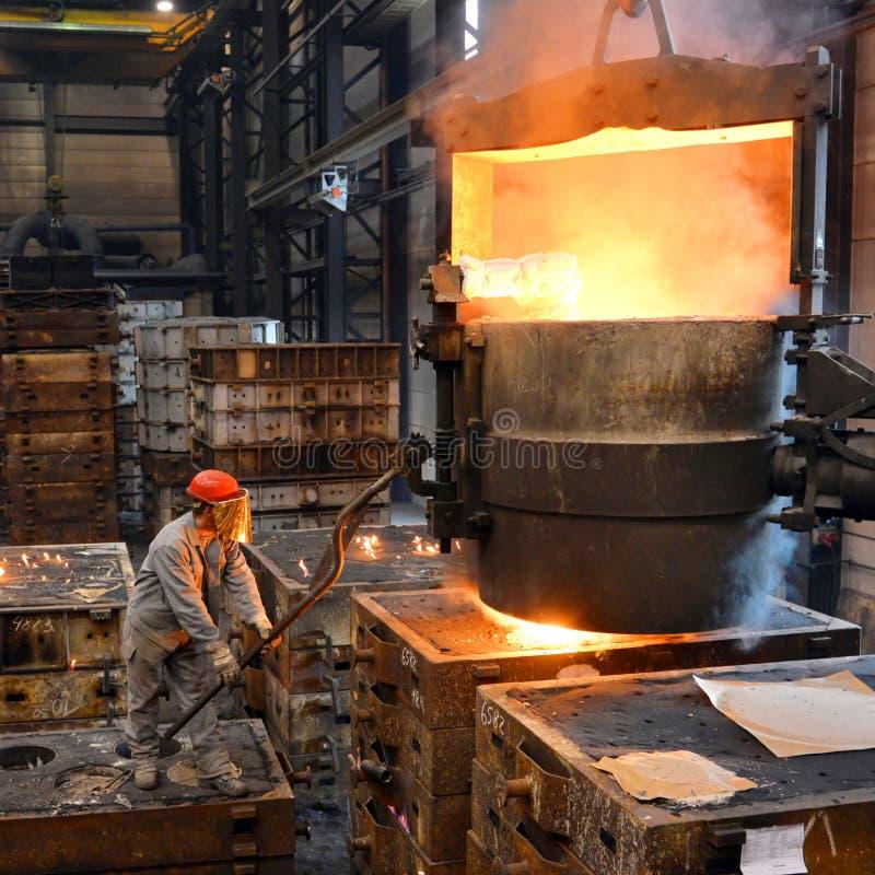 Berlim, Alemanha - 18 de abril de 2013: Produção de componentes do metal em uma fundição - grupo de trabalhadores imagem de stock