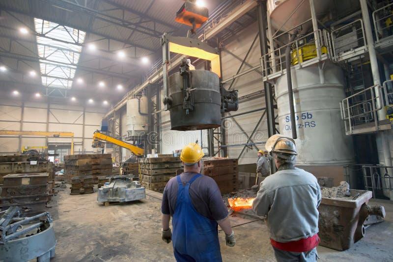 Berlim, Alemanha - 18 de abril de 2013: Produção de componentes do metal em uma fundição - grupo de trabalhadores fotos de stock royalty free