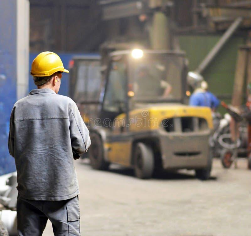 Berlim, Alemanha - 18 de abril de 2013: Produção de componentes em uma fundição - trabalhador do metal imagens de stock royalty free