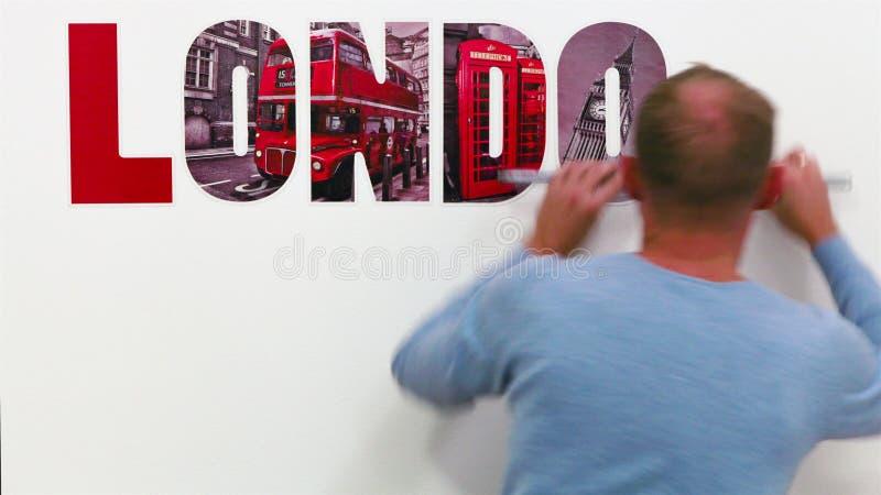 BERLIM, ALEMANHA - 24 DE OUTUBRO DE 2015: Homem novo que desnucleia sua parede da sala branca com palavra de LONDRES o 24 de outu vídeos de arquivo