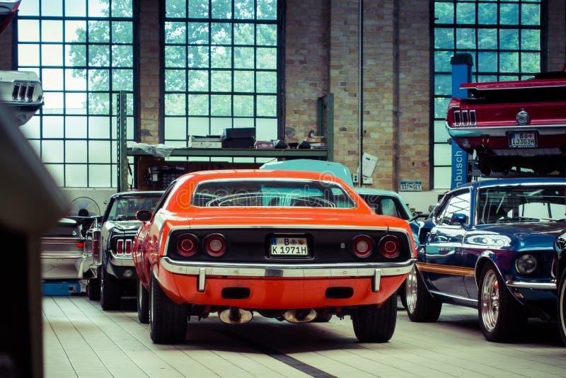 BERLIM, ALEMANHA - em julho de 2017: Garagem do Oldtimer com barracuda e Ford Mustang de Plymouth imagens de stock royalty free