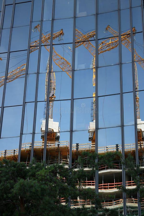 berlim 06/14/2008 Fachada de vidro de uma constru??o com reflex?o de um canteiro de obras Guindastes e andaime imagens de stock