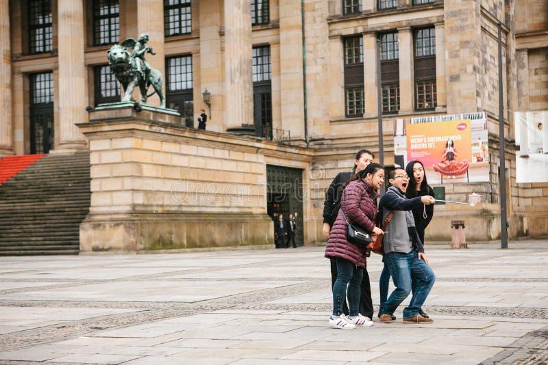 Berlim, o 1º de outubro de 2017: Um grupo de turistas asiáticos desconhecidos faz o selfie ao lado das vistas em um telefone espe foto de stock