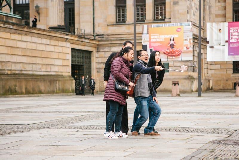 Berlim, o 1º de outubro de 2017: Um grupo de turistas asiáticos desconhecidos faz o selfie ao lado das vistas em um telefone espe fotografia de stock