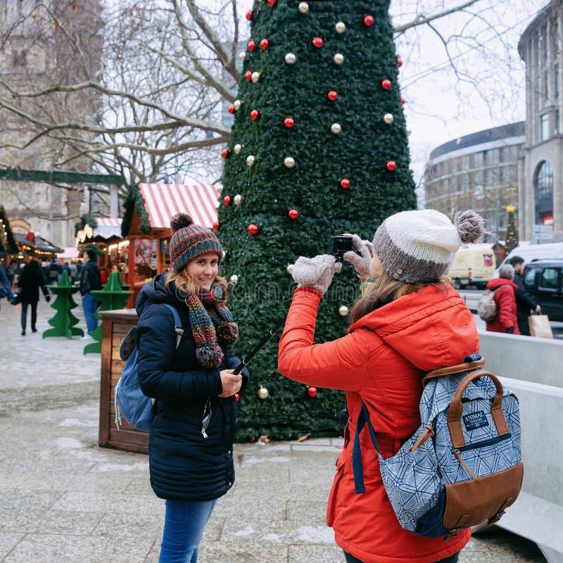 Berlin, Allemagne - 11 décembre 2017 : Filles prenant des photos au marché de Noël chez Kaiser Wilhelm Memorial Church en hiver B photographie stock libre de droits