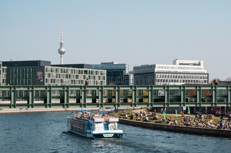 Berlin cityscape with boat on river Spree, people sitting on riv stock photos