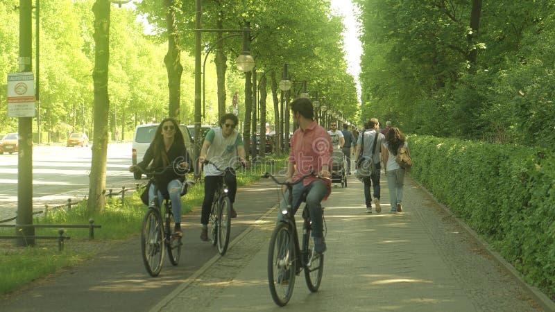 BERLIN, DEUTSCHLAND - 30. APRIL 2018 Leute gehen und fahren Fahrrad entlang dem Weg in berühmtem Tiergarten-Park lizenzfreie stockfotos