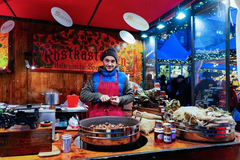 Berlin, Deutschland - 8. Dezember 2017: Mann, der Kastanien am Weihnachtsmarkt bei Gendarmenmarkt im Winter Berlin, Deutschland v lizenzfreie stockbilder
