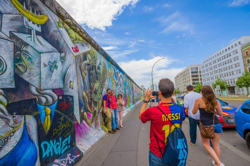 BERLIN, DEUTSCHLAND - 6. JUNI 2015: Turists, das Fotos auf Graffiti Berliner Mauer, Weisen, theirselves auszudrücken macht stockfotos