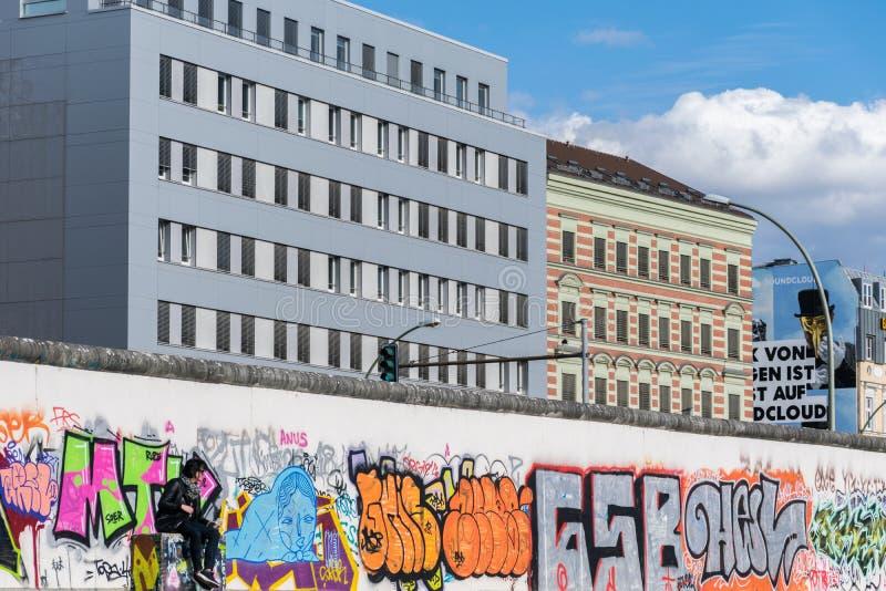 BERLIN, DEUTSCHLAND - 26. September 2018: Szenische Ansicht einer Person, die vor den bunten Graffitis im Berlin sitzt stockfotos