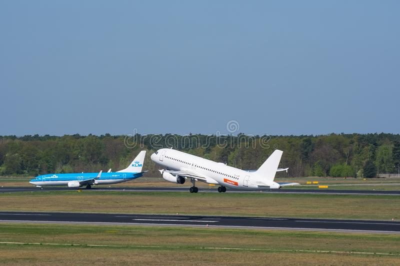 Easyjet Airbus A320 take of at Berlin Tegel while a KLM Boeing 737-800 is taxiing royalty free stock photography