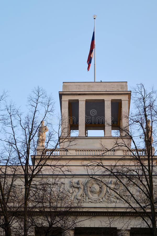 Top of Russian Federation Embassy building. Berlin, Germany - April 14, 2018: Top of Russian Federation Embassy building with flag, statues and USSR coat of arms stock images