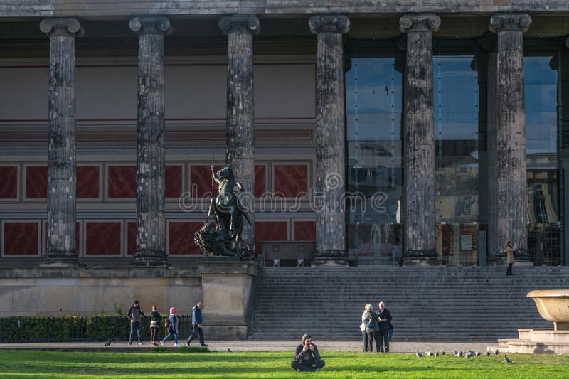 BERLIN, GERMANY - July 28, 2018: man sitting in front of the Altes Museum, its jonic columns and antique statues, and royalty free stock images