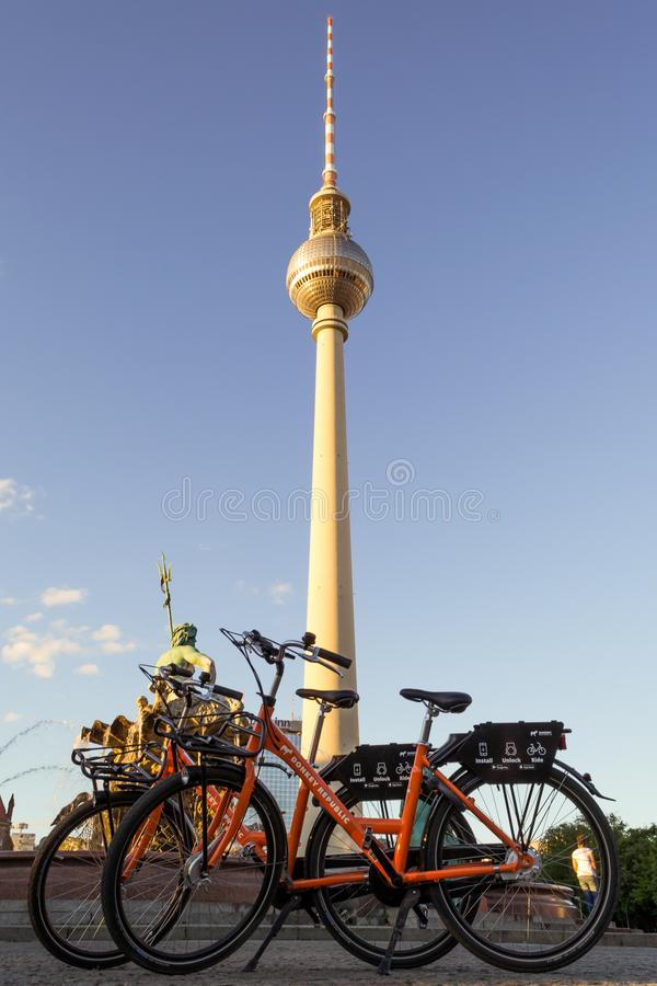 Berlin / Germany - 1 July 2018: Two dockless rental bikes from Donkey Republic bike sharing company in front of the TV Tower royalty free stock photo