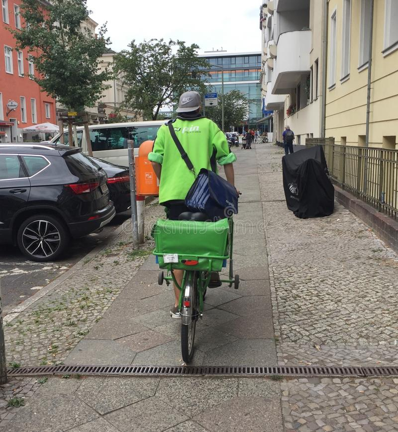 Pin Mail delivery man on green bike. Berlin, Germany - June 20, 2018: Pin Mail delivery man on a green bicycle. Pin Mail AG is a German private postal service royalty free stock image
