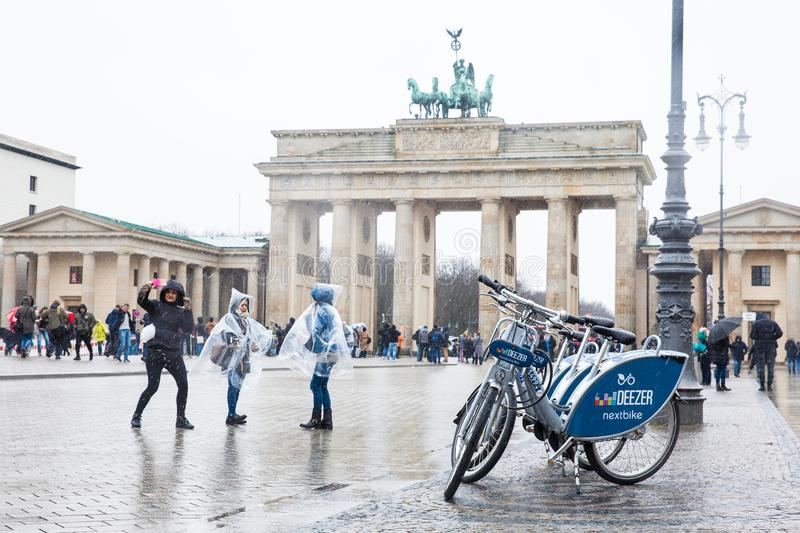 Public bikes and tourists at the Brandenburg Gate viewed from the Pariser Platz on the East side in a snowy end of winter day stock photography