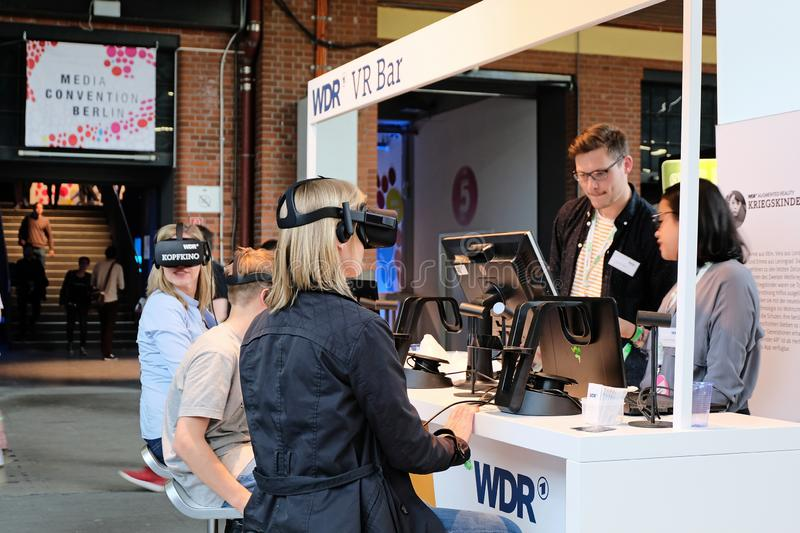 Berlin, Germany - May 3, 2018: Several visitors try VR. Berlin, Germany - May 3, 2018: Several visitors try Virtual Reality glasses at the WDR radio booth during royalty free stock photography