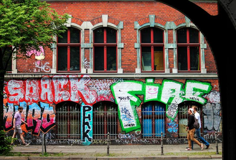 Berlin, Germany - May 14, 2014: side view street with a brick wall full of graffiti and some people walking. Side view street with a brick wall full of graffiti royalty free stock photography