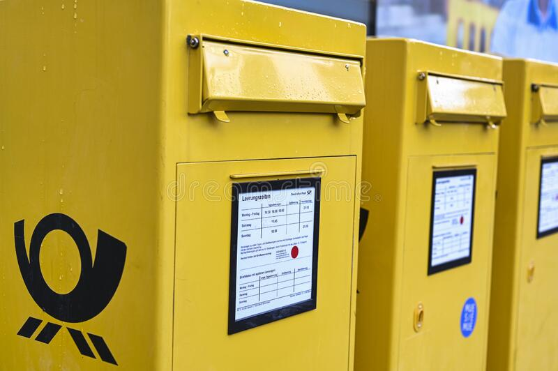Several mailboxes of the German Post on a sidewalk. stock images