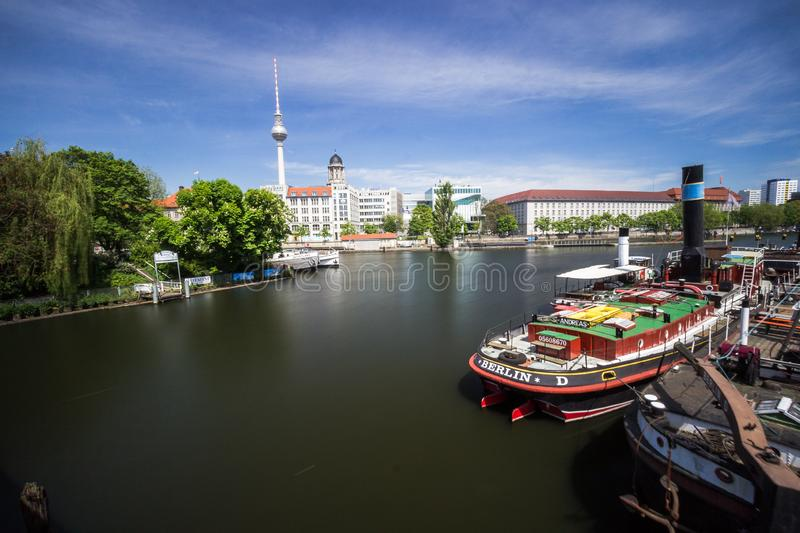9.7.2017 BERLIN GERMANY Old harbor with old ships at the riverside in Berlin, Germany. In The background is the berlin TV-Tower stock image