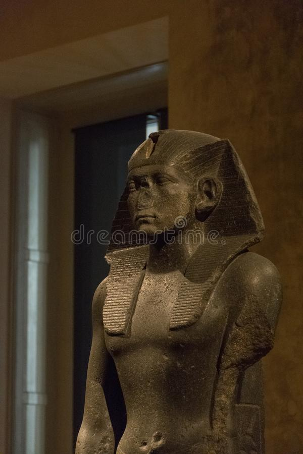 BERLIN, GERMANY - SEPTEMBER 26, 2018: Zoomed in dark and profile picture of the Praying statue of the pharaoh king. Amenemhet III, ruler of a Egypt Dynasty, at stock images