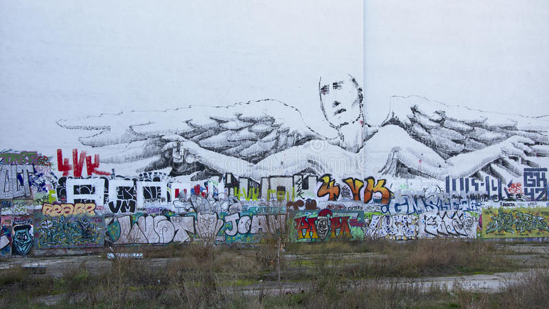 Berlin graffiti wall with man with wings stock photography