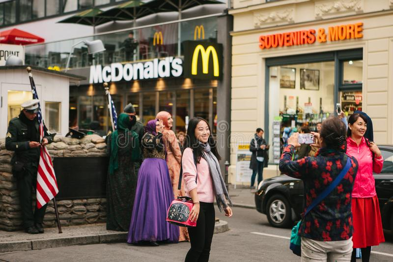 Berlin, October 1, 2017: Asian tourists are photographed next to a famous city attraction called Chekpoint Charlie royalty free stock images
