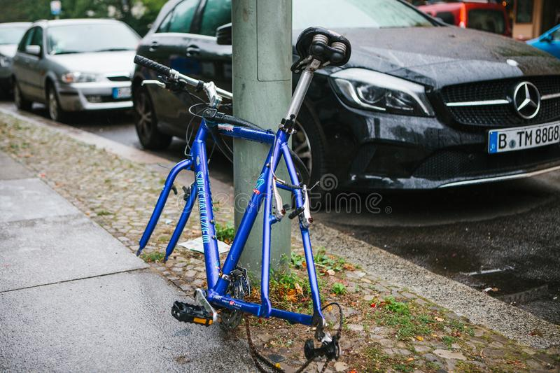 Berlin, October 2, 2017: Blue bicycle attached to street pillar with lock stands without wheels after being stolen in. Blue bicycle attached to street pillar stock photo