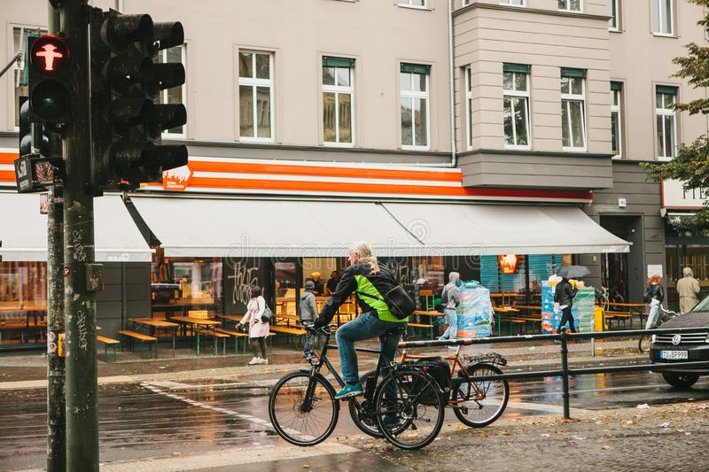 Berlin, October 1, 2017: An elderly man on a bicycle stands on a red traffic light and waits for him to go. Ordinary royalty free stock photo