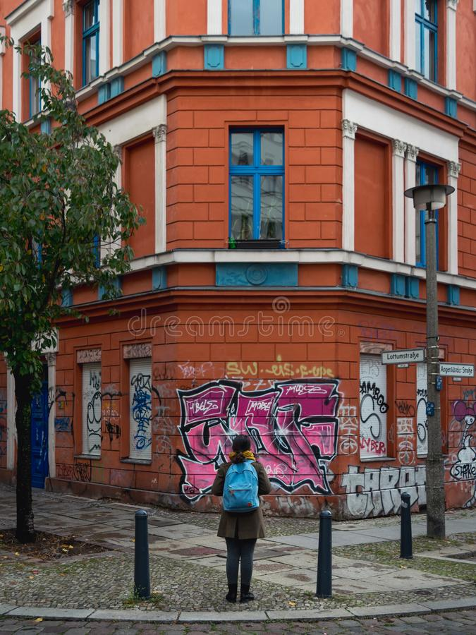 BERLIN - OCTOBER 19, 2016: A girl admiring the graffiti and architecture royalty free stock image
