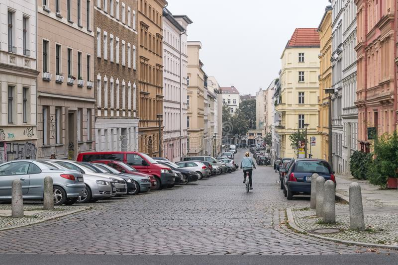 BERLIN - OCTOBER 18, 2016: A girl on a bike rides down a beautiful street stock image
