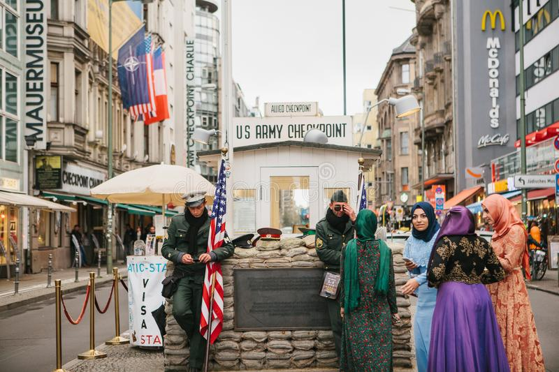 Berlin, October 1, 2017: Positive Arab women`s tourists next to the famous city attraction called Chekpoint Charlie stock photography