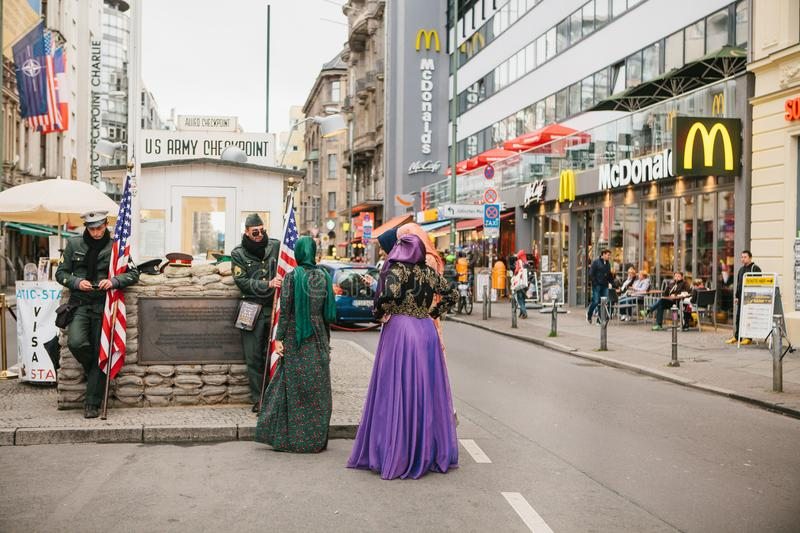 Berlin, October 1, 2017: Positive Arab women`s tourists next to the famous city attraction called Chekpoint Charlie stock image