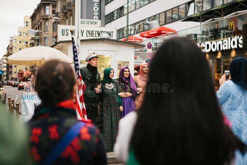 Berlin, October 1, 2017: Positive Arab women tourists are photographed next to a famous city attraction called Chekpoint royalty free stock photography