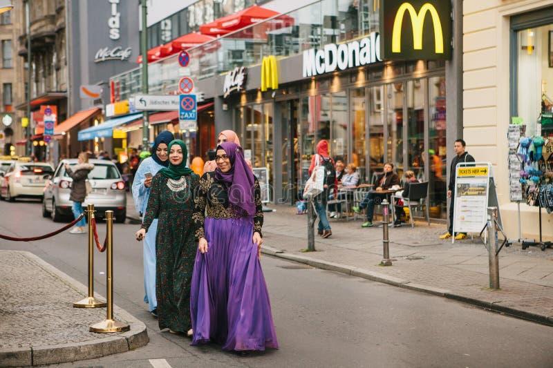 Berlin Oktober 1, 2017: Grupp av positiva kvinnor - arabiska flyktingar i medborgaredräkter med dyrt gå för telefon arkivbilder