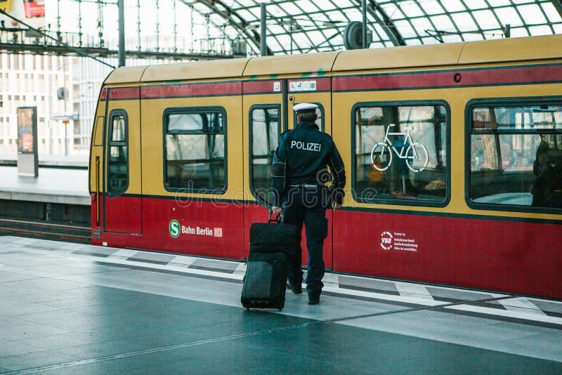 Berlin, Październik 03, 2017: Policjant z wodzem iść pociąg opuszczać Demobilizacja, wakacje zdjęcie royalty free