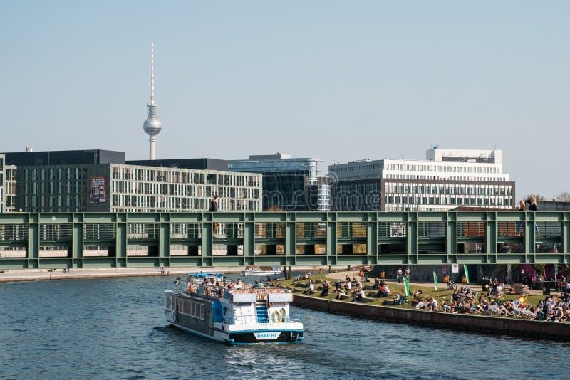 Berlin-Stadtbild mit Boot auf Fluss Gelage, Leute, die auf riv sitzen stockfotos