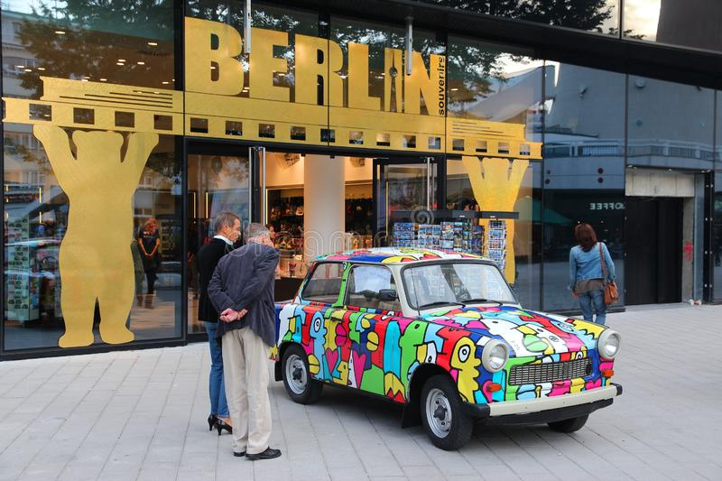 Berlin symbols. BERLIN, GERMANY - AUGUST 25, 2014: People admire Colorful Trabant 601 car parked in Berlin. 3,096,099 Trabant cars were produced despite their stock photos