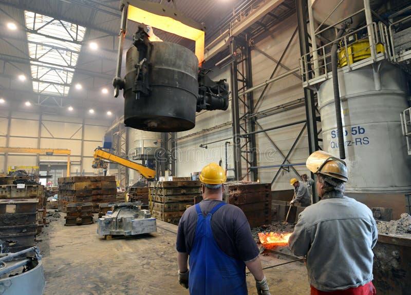 Berlin Tyskland - April 18, 2013: Produktion av metalldelar i en gjuteri - grupp av arbetare royaltyfria bilder
