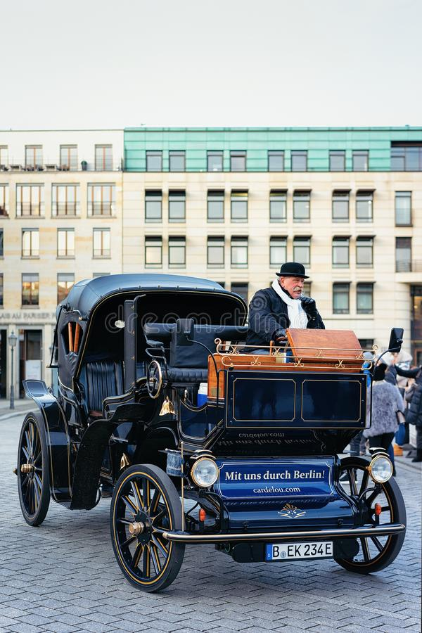 Berlin Tyskland - December 13, 2017: Chaufför och hans elektriska vagn i gatan av Berlin, Tyskland Svart bil för tappning arkivbilder